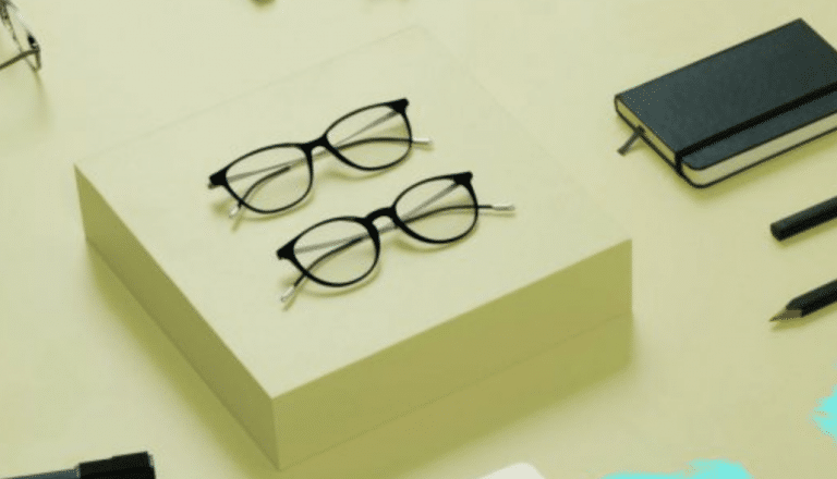 Two Moleskine eyeglass frames and a notebook on a green background