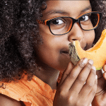 Smiling young girl wearing black and orange glasses holds up a piece of cantaloupe