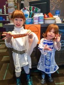 Two trick-or-treaters holding reflective stickers in our Millstream store